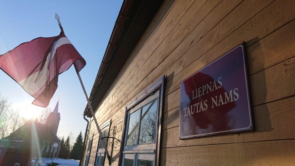 Folkets hus i Liepna och den lettiska flaggan i en flaggstång på väggen.